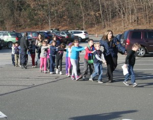 The now-iconic photo of Connecticut state police evacuating children, eyes closed, from Sandy Hook Elementary. Photo by Shannon Hicks of the Newtown Bee.